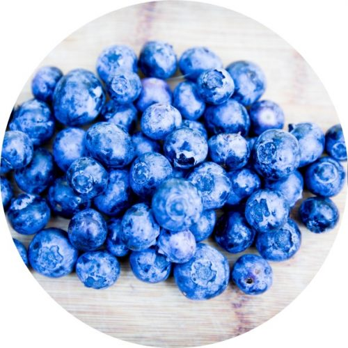 Handful of blueberries on wooden board