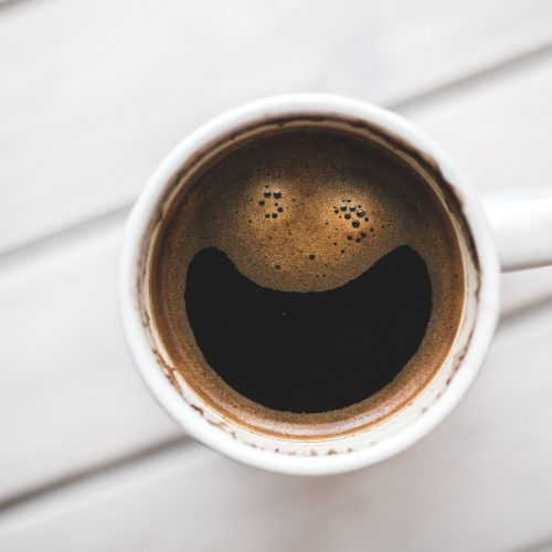 A cup of coffee with a smile in the crema.