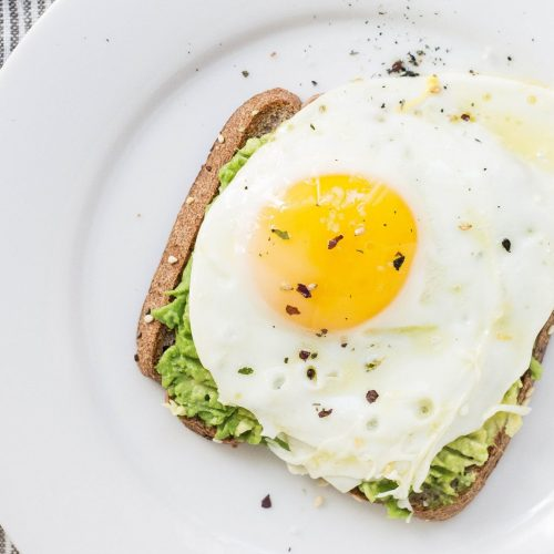 An egg on toast on a crisp white plate; a great source of the macronutrient protein.