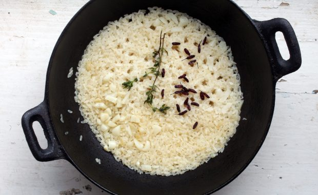 Rice cooking in a big pot with spices.