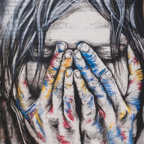 Graffiti style painting of a person clutching at their face as though in distress.